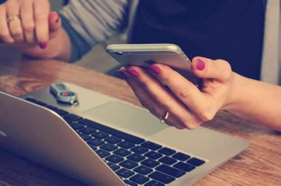 Femme devant un ordinateur portable un téléphone à la main