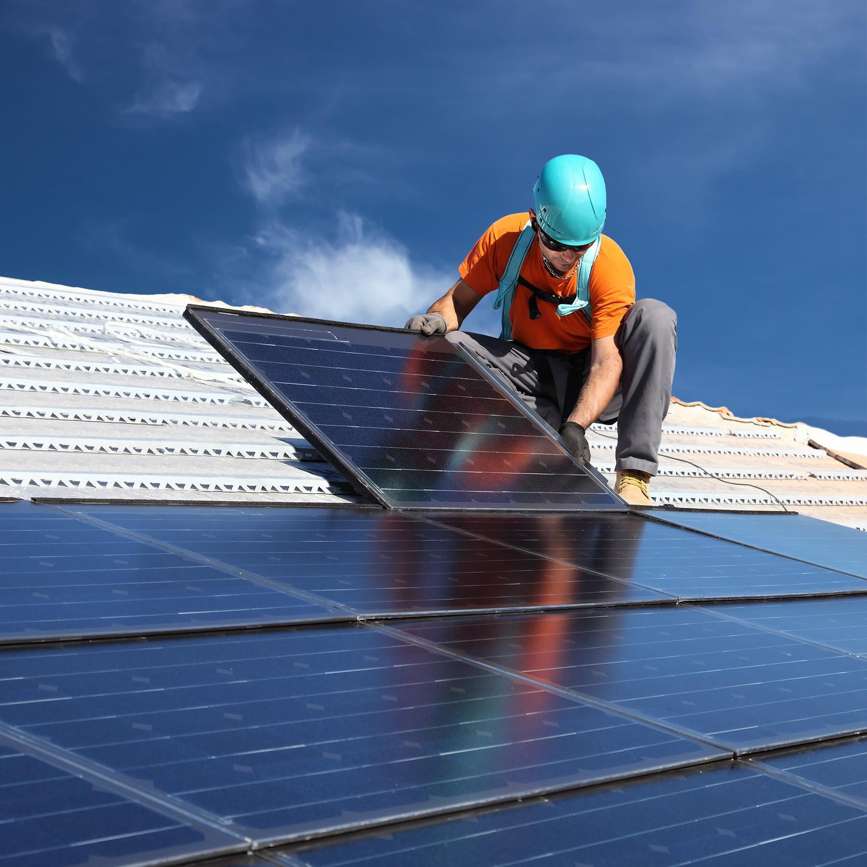 Homme installant des panneaux solaires