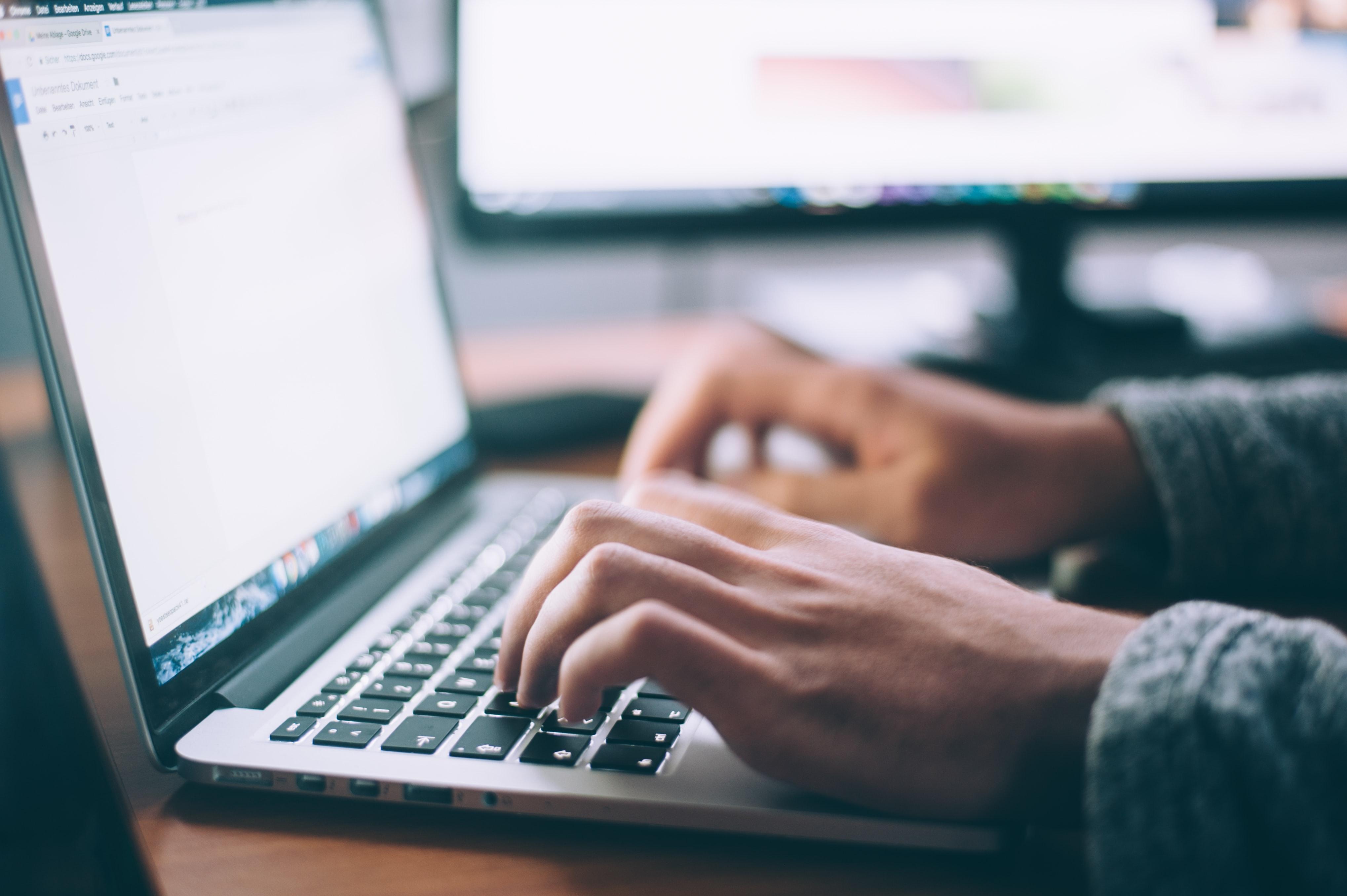 Homme tapant sur le clavier d'un ordinateur portable