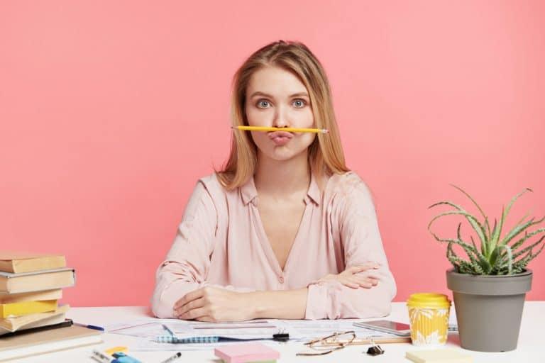 Femme tenant son crayon au dessus de sa bouche