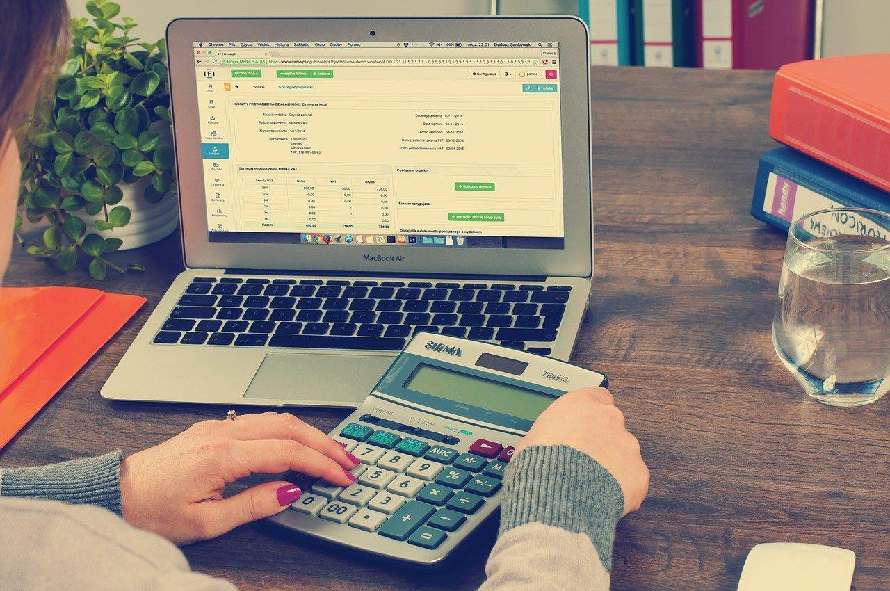 Femme sur son ordinateur avec calculatrice dans les mains