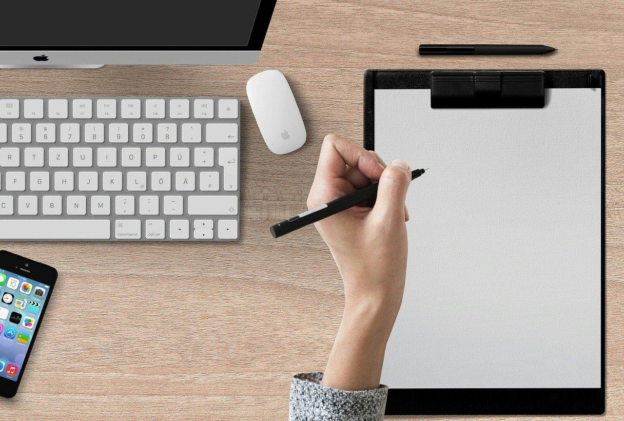 Main avec stylo et bloc note